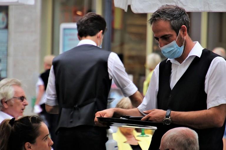 Cameriere con mascherina prende ordinazioni al bar